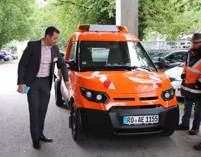 Bild von einem orangenen Streetschooter und zwei Männern, welche diesen begutachten. Ein Mann steht rechts und trägt einen Anzug. Der andere Mann auf der linken Seite trägt eine lange Warnweste und Jeans.
