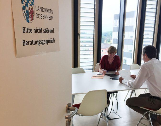 """Foto von einer Beratungssituation im Landratsamt Rosenheim. Im Hintergrund sind eine Frau und ein Mann zu sehen, welche an einem Tisch sitzen. Im Vordergrund kann man eine offene Tür erkennen, an welcher ein Schild hängt mit der Aufschrift """"Bitte nicht stören! Beratungsgespräch"""""""