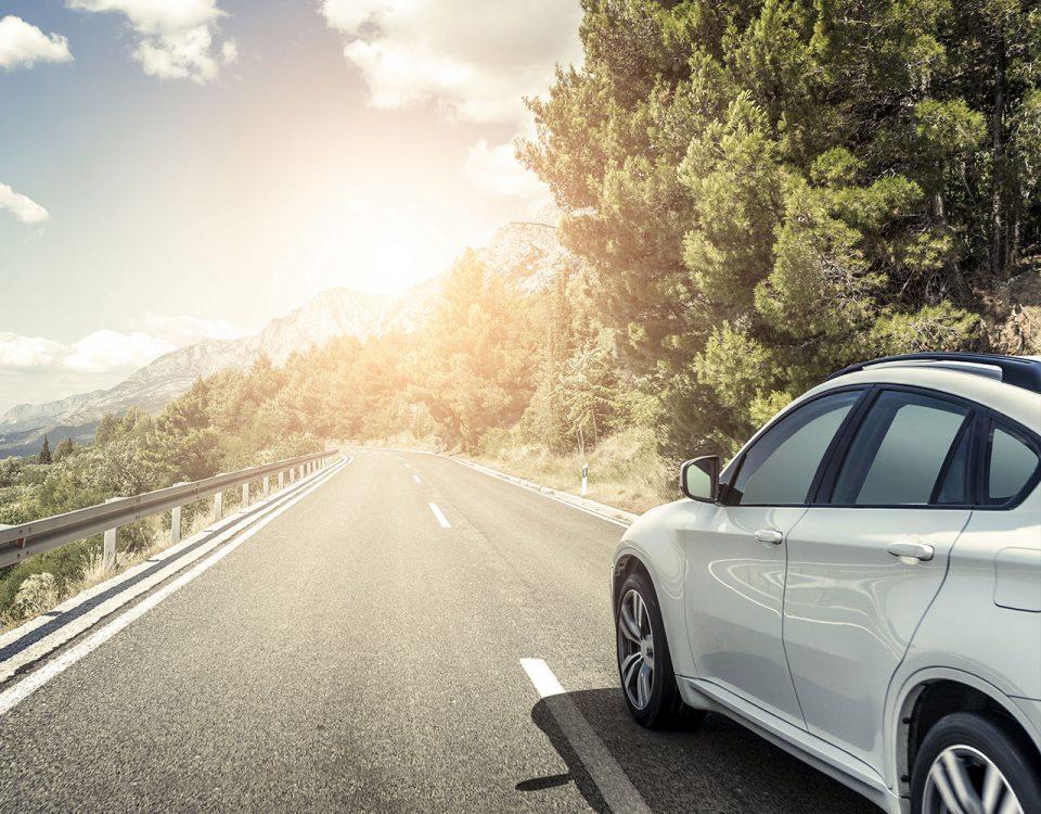 Rein dekoratives Element. Zu sehen ist im Anschnitt auf der rechten Seite ein weißes Auto, welches auf einer Straße in den Bergen fährt. Am rechten Straßenrand erkennt man üppige Wälder, am linken Straßenrand eine Leitplanke und einen leichten Abhang. Im Hintergrund sind die Berge zu sehen.