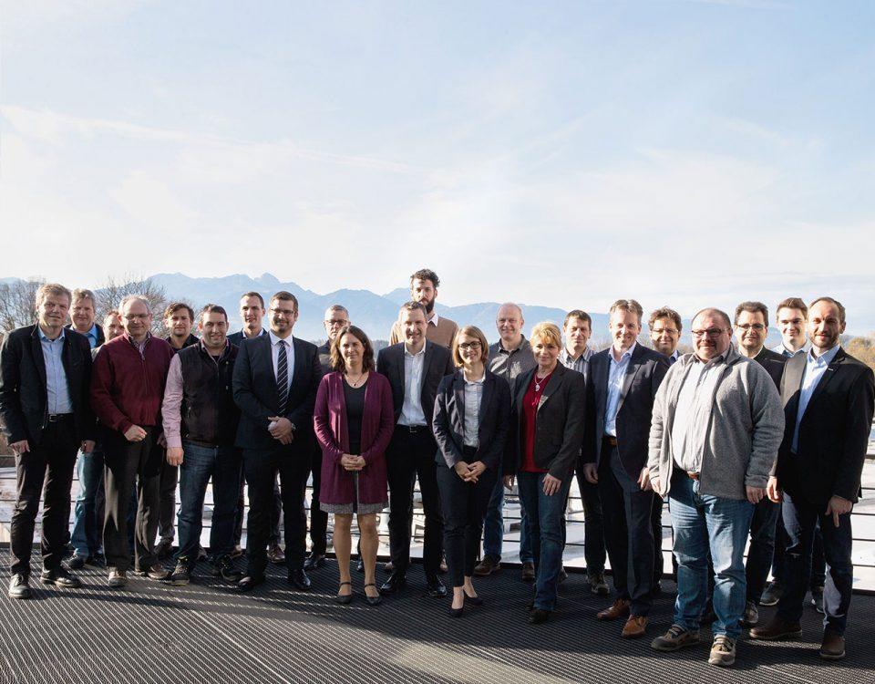 Auf dem Bild sind 22 Personen zu sehen, die freundlich in die Kamera lächeln. Die meisten tragen einen Anzug. Im Hintergrund sind die Berge und ein blauer, leicht bewölkter Himmel zu erkennen.