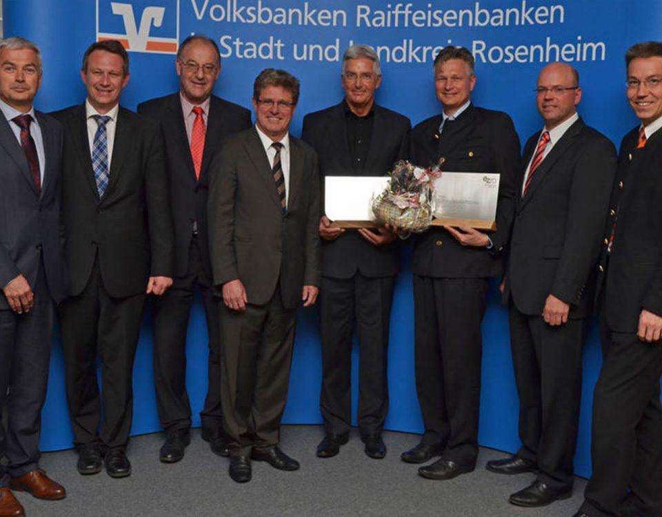 Foto von der Preisverleihung des Energiezukunftspreises 2015. Zu sehen sind 8 Männer. Zwei davon halten einen Preis in der Hand aus Metall und Holz.