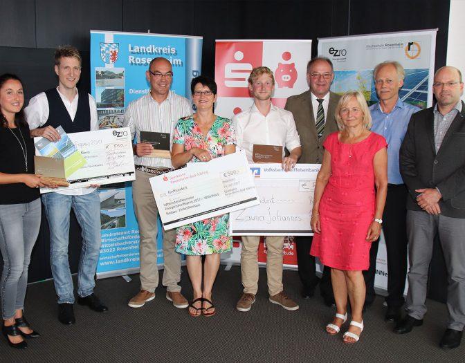Foto von der Preisverleihung des Energiezukunfspreises 2017. Zu sehen sind 9 Personen, davon zwei Frauen und sieben Männer. Die Gewinner sind jeweils mit einem aus Holz und Metall gefertigten Preis zu sehen, sowie mit einem Scheck über 500 Euro.