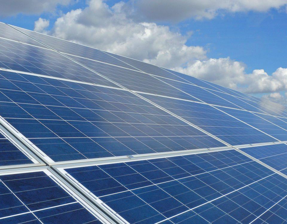 Rein dekoratives Element. Das Foto zeigt eine große Fläche mit Photovoltaik-Anlagen. Außerdem kann man im Hintergrund einen leicht bewölkten, aber blauen Himmel erkennen.